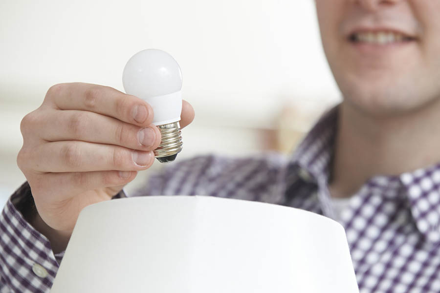 Man Putting Low Energy LED Lightbulb Into Lamp At Home