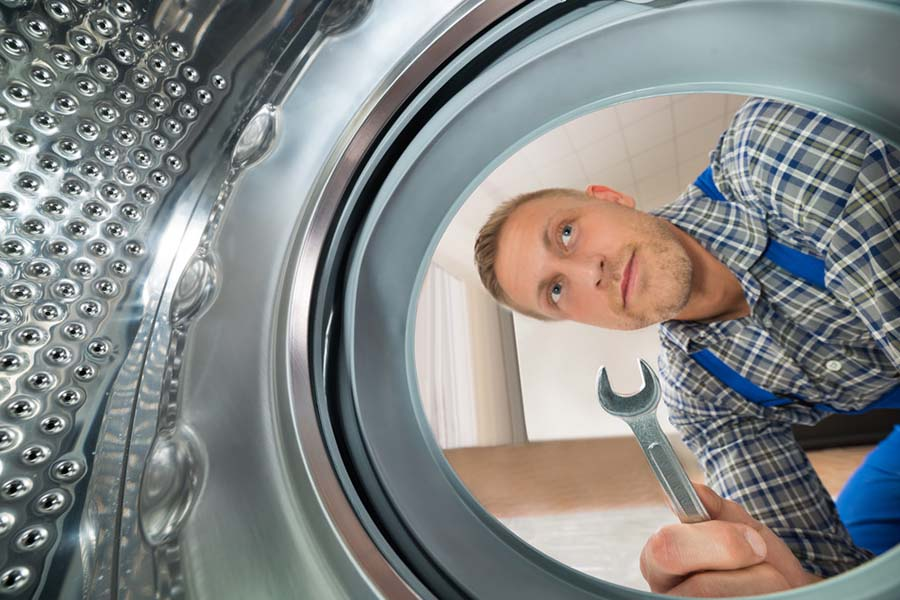 Man with tools looking inside a front loading dryer