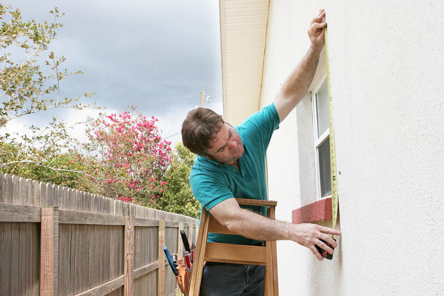 Person works on windows on exterior of a house