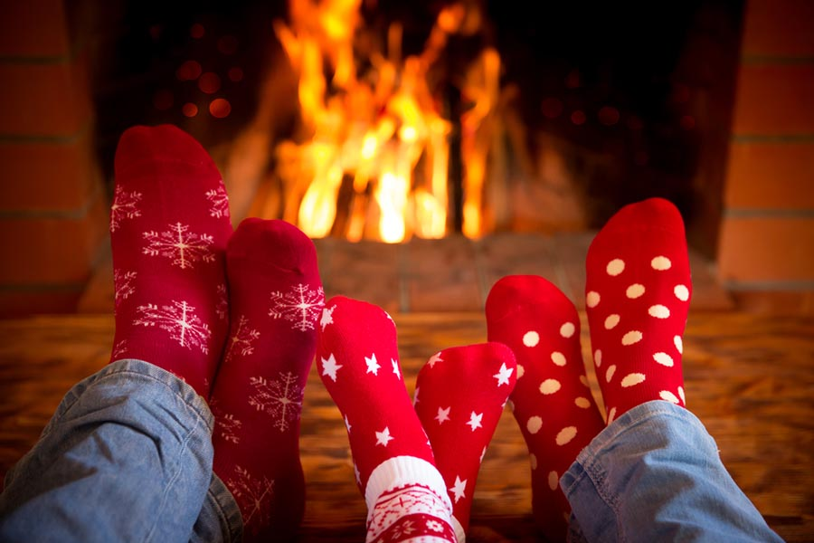Family with red socks on in front of a fireplace