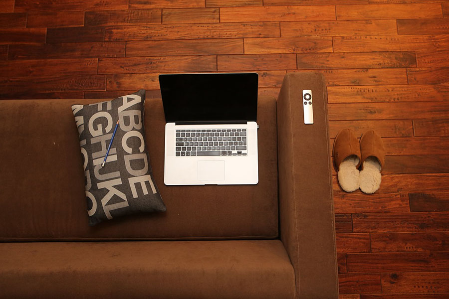 Laptop and other personal belongings on a brown couch