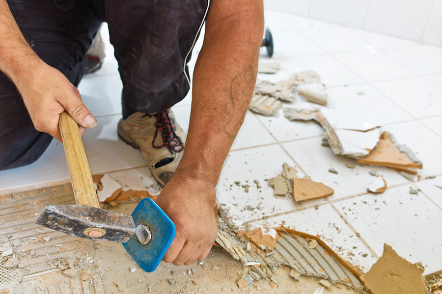 Person hammers a floor with a tool