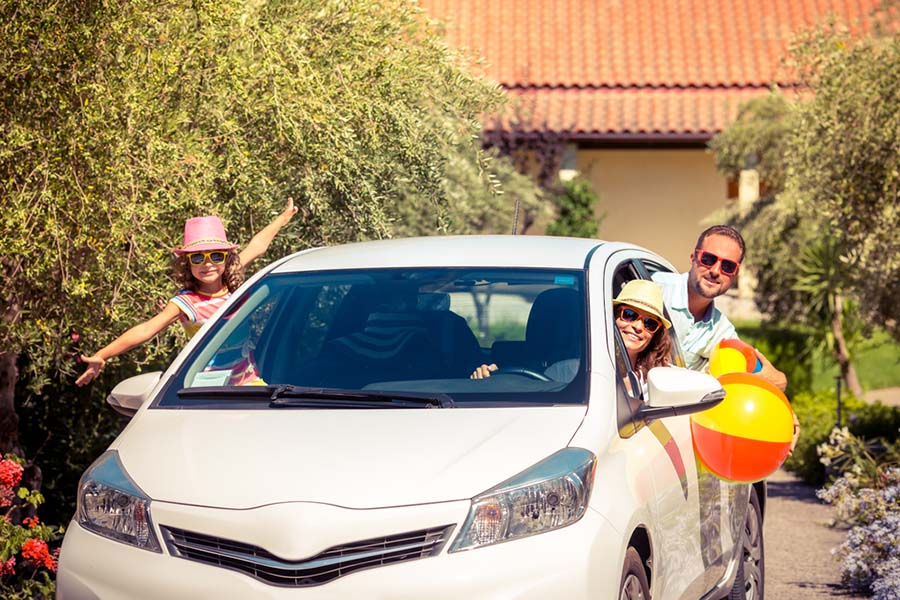 Family smiling in a four door car in a driveway