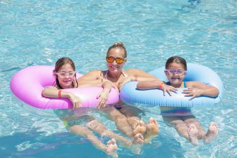 A mum and two daughters in the pool