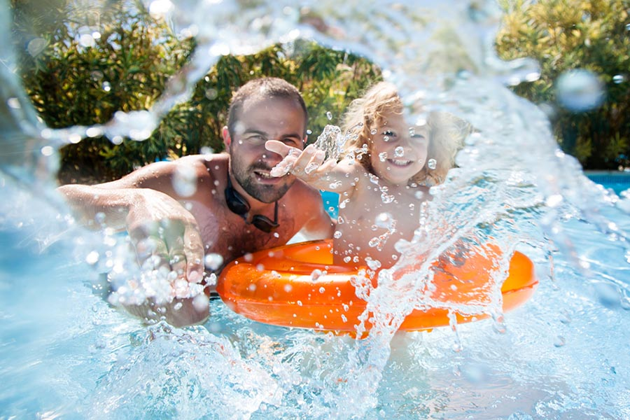 Father and daugther playing in a pool, splashing around
