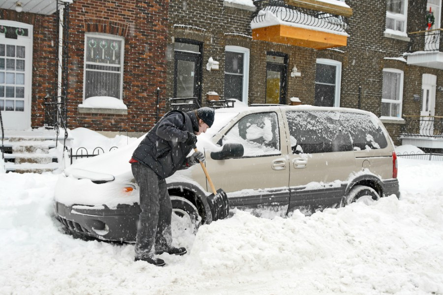 Person sholves their van out of the snow in the city
