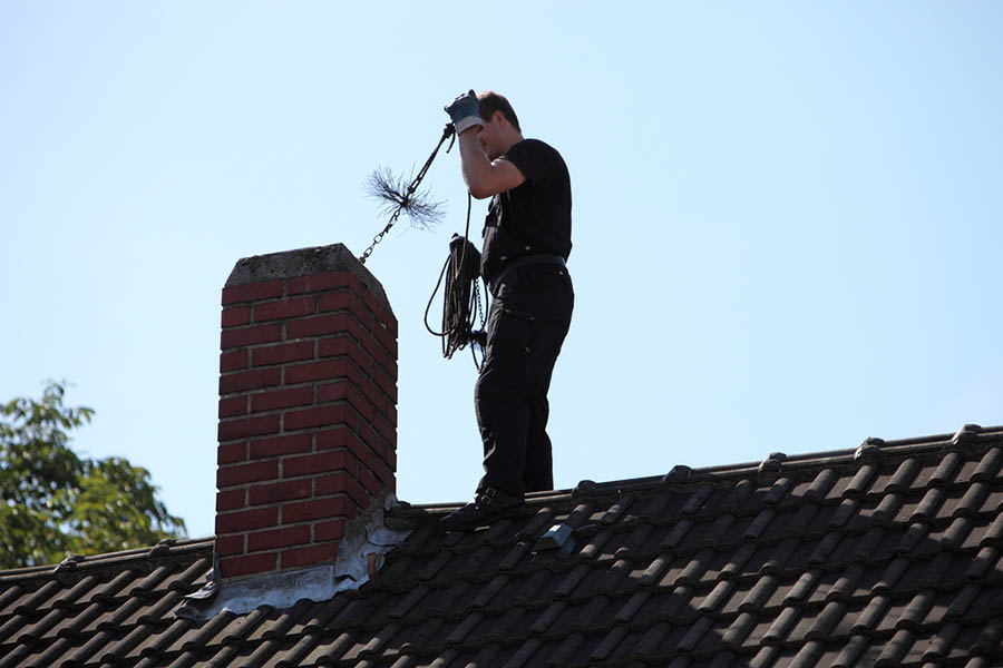 A man stands on a roof and cleans a chimney for a wood stove