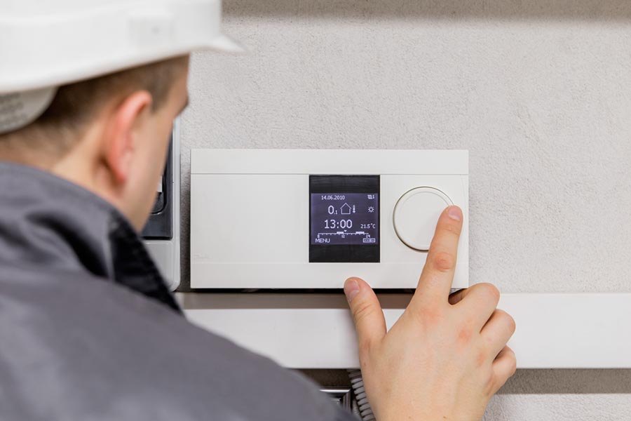 Construction worker controlling a digital thermostat.