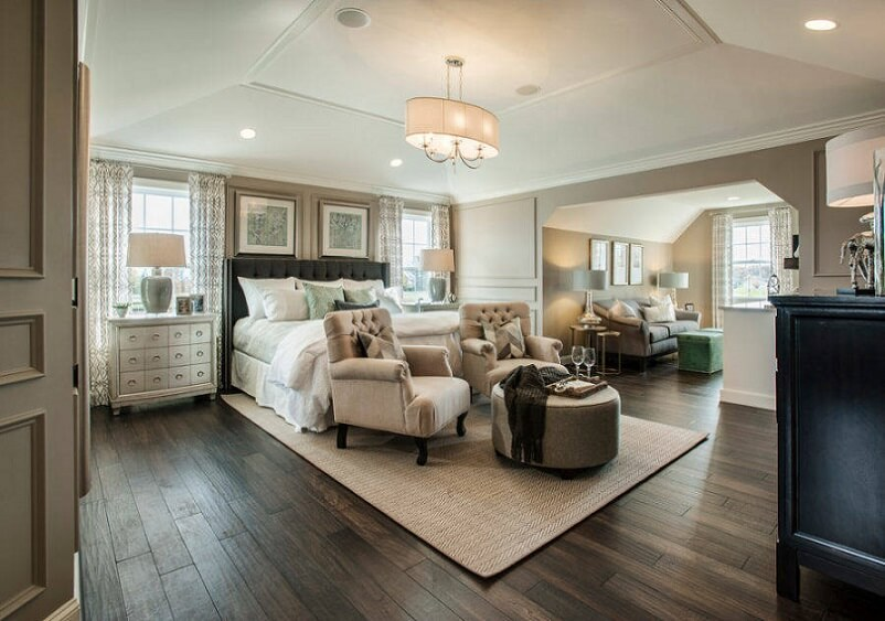 Master bedroom with light furniture and dark floors