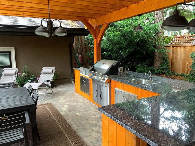 Outdoor kitchen with stone countetops and wood roof