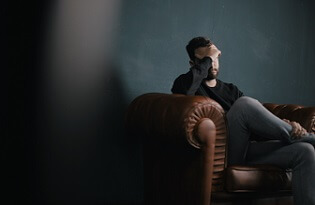 Man sits on the couch in a dark room, sad.