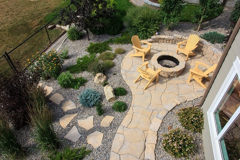Aerial view of a stone patio with a fireplace and seating