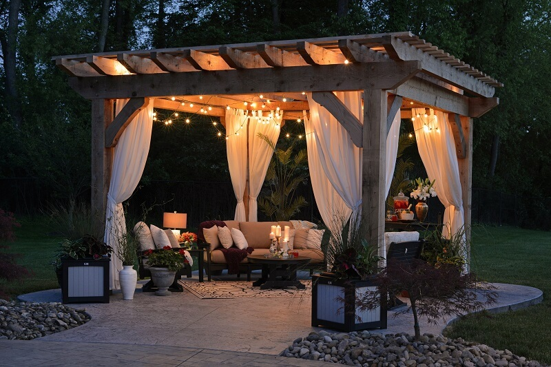 Gazeebo and patio space with hanging lights at night