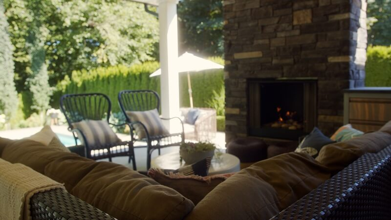 Wicker and aluminum patio furniture by a stone fireplace
