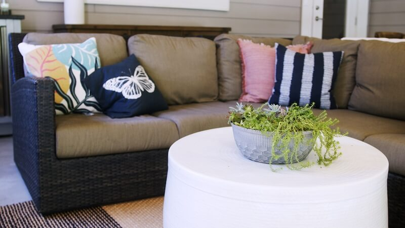Outdoor couch and throw pillows near a table