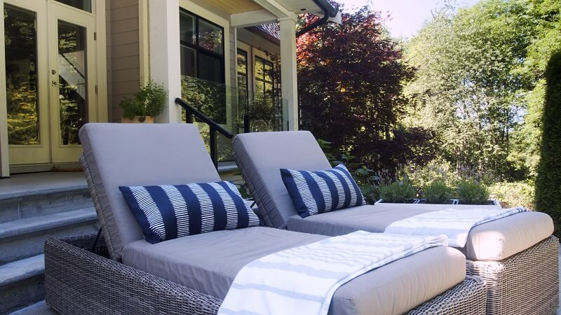 Outdoor resin wicker lounge chairs in the sun