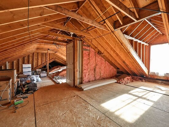 Unfinished home attic with exposed insulation
