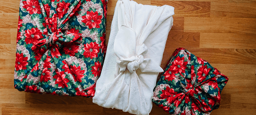 Holiday gift wrapped in white fabric