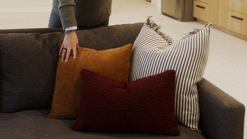 Three different size throw pillows arranged on a sofa