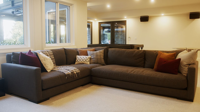 Several cushions arranged on an L-shaped sectional sofa