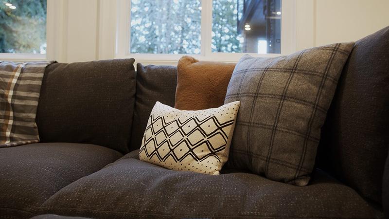 Three pillows arranged on a dark sofa